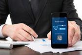 Podnikatel v kanceláři drží telefon s onlain nakupovat o