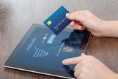 Kvinnliga händer med kreditkort och en tablett på kontoret ochΓυναικεία χέρια που κρατούν την πιστωτική κάρτα και ένα δισκίο στο γραφείο και