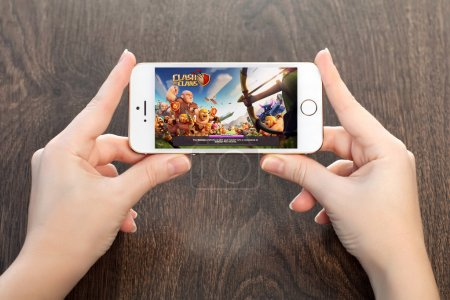 female hands holding a white iPhone with Clash of clans on the s
