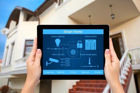 Photo pour Femelles mains tenir une tablette PC avec maison intelligente de système sur un écran sur le fond de la maison - image libre de droit