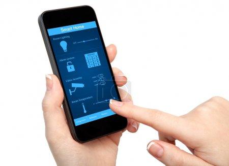 Photo pour Femme isolé main tenir le téléphone avec la maison intelligente de système - image libre de droit