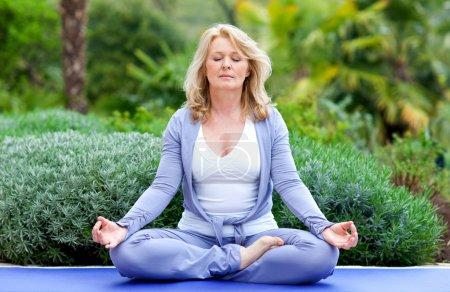Photo pour Femme mature faisant des lotus yoga positio dehors dans le jardin - image libre de droit