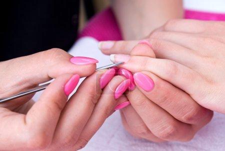 Photo pour Femme main sur le traitement de manucure avec couteau à cuticule dans le salon de beauté - image libre de droit