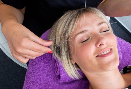 Beautician makes threading hair removal procedure ...