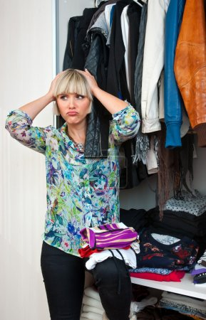 Photo for Attractive woman in front of closet full of clothes - Royalty Free Image