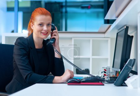 attractive business woman in office on phone