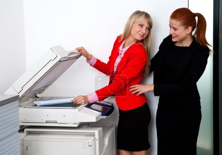 two woman colleagues working on printer in office