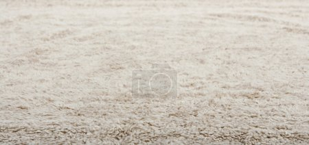 Photo for Low close up view of a beige furry carpet texture background, full frame. - Royalty Free Image