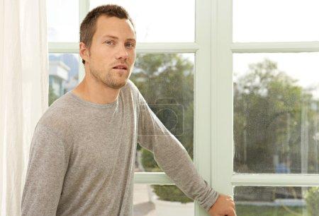 man standing by garden doors at home.