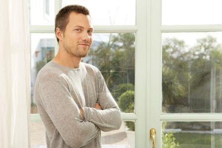 man standing by garden doors at home