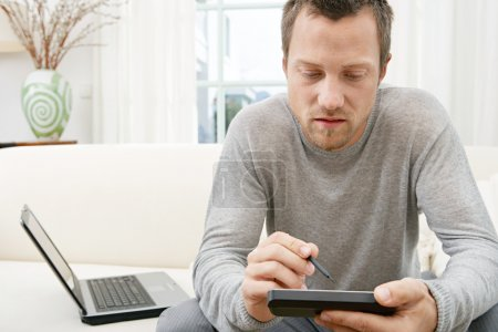 Young using technology while sitting on a white sofa at home.