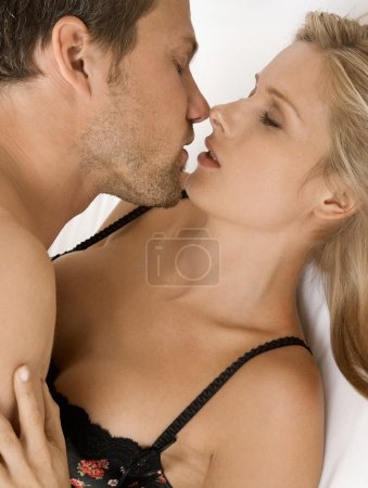 Close up of young couple hugging and kissing with their eyes closed.