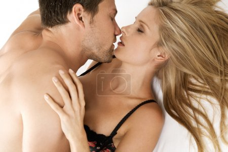 Young couple hugging and kissing with their eyes closed.