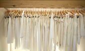 Line of white clothes hanging on wooden hangers in a fashion store.