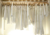 Line of new white clothes hanging on wooden hangers in a fashion store.