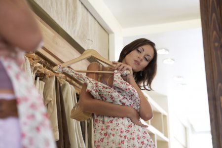 Close up of a young attractive woman trying on a dress in a fashion store