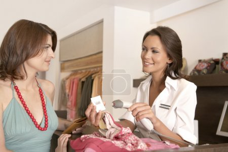 Female client shopping at fashion store with shop assistant reading a label with a barcode reader.