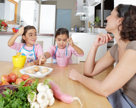 Mother teaching twin daughters to beat eggs in the kitchen