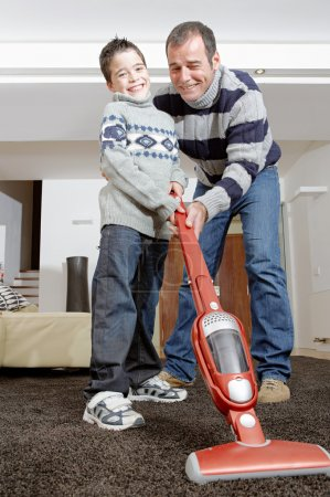 Dad and son vaccum cleaning their living room, smiling and bonding.
