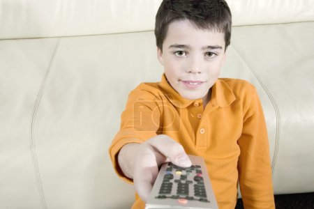 Young boy using a tv remote control while watching television at home.