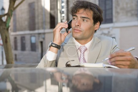 attractive professional businessman using a cell phone and taking notes while on a phone call conversation in a car park