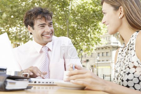 Photo for Two business having a meeting in an outdoors cafeteria in the city, smiling. - Royalty Free Image