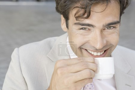 Attractive young businessman smiling at the camera while drinking a cup of coffee outdoors.