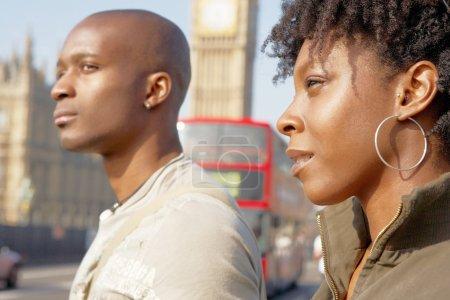 attractive black tourist couple walking past Big Ben