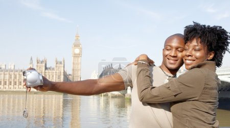 Photo for Panoramic view of a young african american couple taking pictures of themselves while on vacations in London, standing in front of Big Ben. - Royalty Free Image