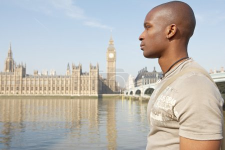 Profile view of a young tourist walking by Big Ben whilst visiting London city.