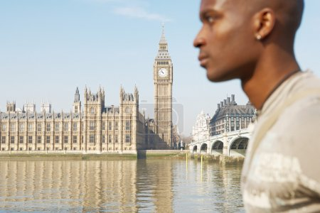 Wide view of Westminster Palace and the river Thames with a tourist walking past out of focus.