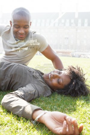 african american couple talking as they relax laying down on green grass