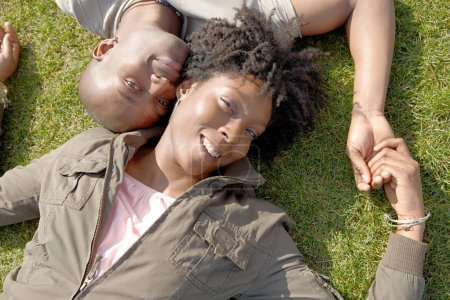 Over head view of an attractive black couple laying down on green grass