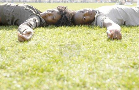 Photo pour Couple africain-américain portant sur l'herbe verte dans la ville. - image libre de droit