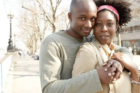 attractive african american couple visiting London and hugging