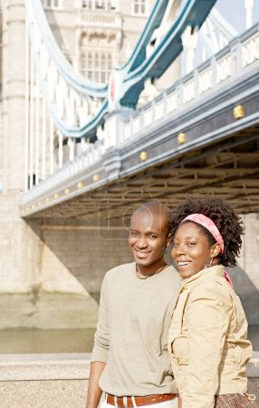 Attractive african american couple walking passed Tower Bridge in London