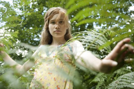 Teenage girl peering through forest foliage, looking into the camera.