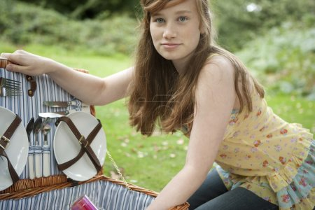Teenage girl opening a picnic basket.