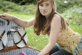 Teenage girl opening a picnic basket.