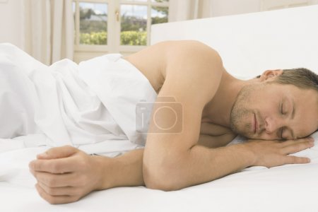 Attractive young man sleeping in a white linen bed.