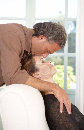 Photo for Mature man kissing woman's forehead while lounging at home's living room. - Royalty Free Image