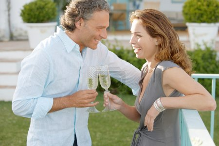 Mature couple toasting with champagne while in vignard's garden.