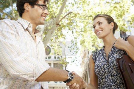 Photo pour Gros plan d'une businessmand et une femme d'affaires, se serrant la main de la ville, souriant. - image libre de droit