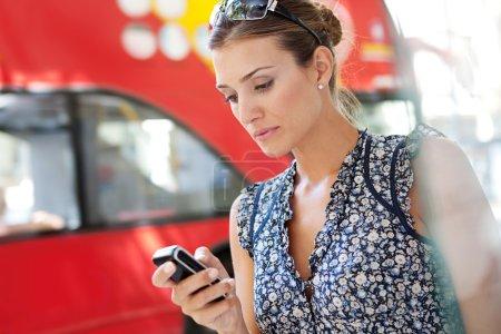 Photo pour Portrait d'une femme d'affaires au transport attrayant à l'aide de son téléphone intelligent dans la ville près d'un arrêt de bus. - image libre de droit