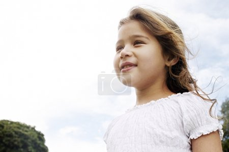 Aspirational portrait of a young girl smiling in the park with her hair blowing in the wind.