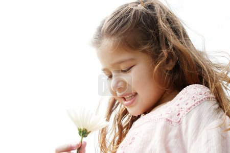 Close up portrait of a young girl holding a white daisy flower in her hand against the sky