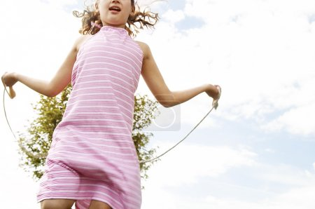 Young girl skipping in the park with a rope.