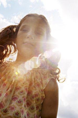 Photo pour Portrait d'une fille contre le ciel bleu avec des rayons de soleil et une fusée éclairante . - image libre de droit