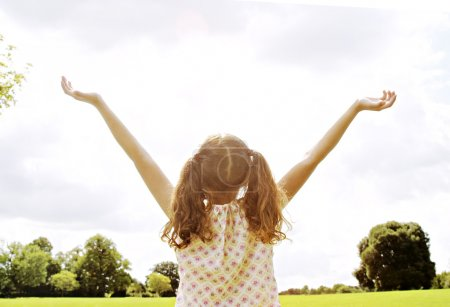 Girl standing in the park with her arms outstretched towards the sky.