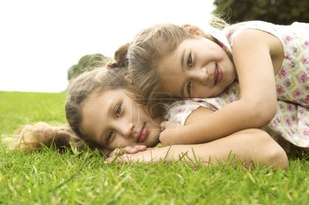 Two sisters laying down on top of each other and smiling in the park.